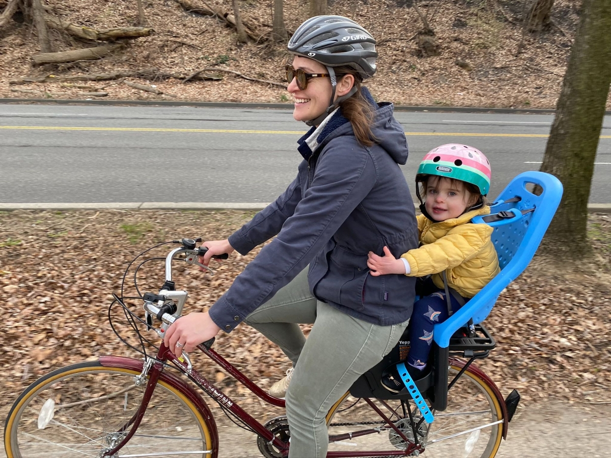 woman biking with a toddler