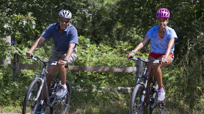 President Obama and the first family cycle together on vacation.  Credit: AP Photo/Jacquelyn Martin